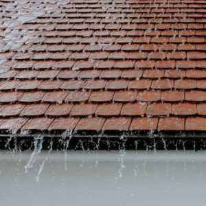 rain spilling off of a brown shingled roof