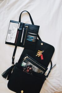 A handbag laying on its side with contents spilling out